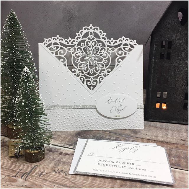 Christmas Wedding Invitations. Finding the perfect balance between  Wedding elegance with a Christmas theme… These invitations were hand die cut. Crisp white card, hand embossed falling snow added to the front, finished with silver ribbon, a delicate silver glitter snowflake, and a single pearl